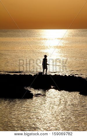 Fisherman on beach / Lonely fisherman on beach as the sun sets .