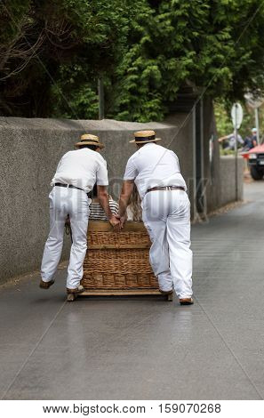 Toboggan riders moving traditional cane sledge downhill on the streets of Funchal. Monte park Madeira island Portugal