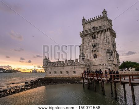 LISBON PORTUGAL - NOVEMBER 24 2016: Torre de Belem on the bank of Tagus river in Lisbon Portugal at sunset.