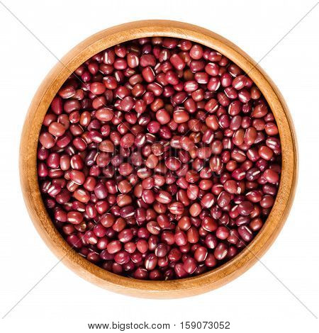 Red adzuki beans in wooden bowl, also called azuki, aduki or Red Mung Bean. Dried small beans of Vigna angularis. Isolated macro food photo close up from above on white background.