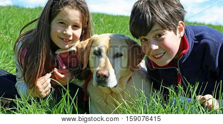 Young Boy And Little Girl With Labrador Retriever Dog