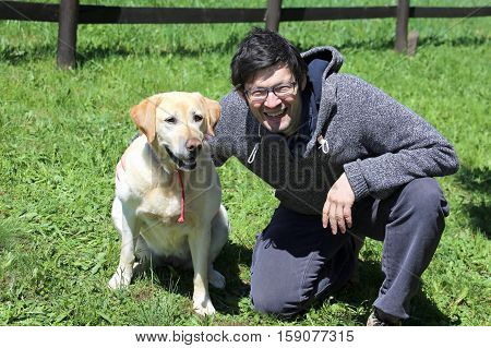 young man with blacks hair smiling with his labrador dog