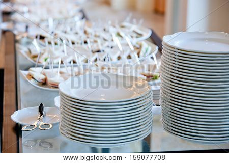 a stack of white plates on a glass banquet table against the background of the dishes with small sandwiches
