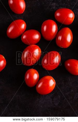 Top View On Several Red Cherry Tomatoes On Black Board