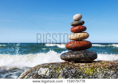 Concept of harmony and balance. beautiful pyramid of colorful wet pebbles . Rock Zen in the background of the sea