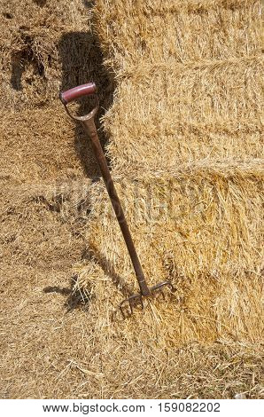 Close up of a pitchfork and hay bales