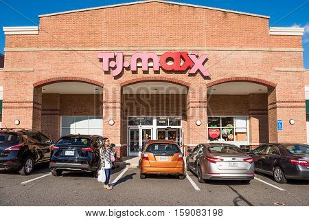 Fairfax, USA - November 27, 2016: TJ Maxx store facade in downtown in Virginia city with brick architecture and parked cars with person