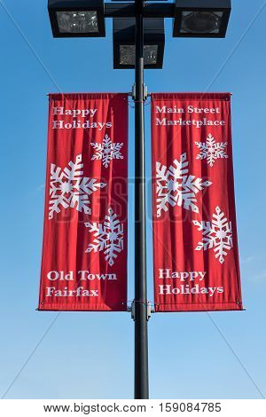 Fairfax, USA - November 27, 2016: Happy holidays red banner on lamp post in downtown old town city in Virginia with snowflakes