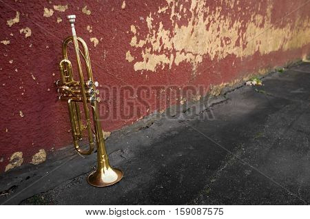 Old worn trumpet stands alone against a grungy pealing brick wall