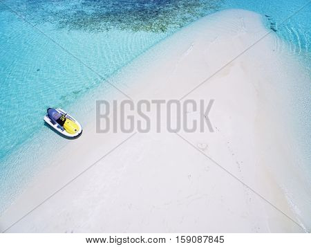 Landscape seascape aerial view over  Maldives Male Atoll sandbank island. Jet ski at the white sandy beach