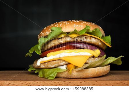 A delicious huge burger with two cutlets on a wooden board on a dark background. Photo causing appetite. The concept of fast food delicious food but unwholesome.