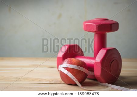 Apple And Measuring Tape And Pair Of Red 1 Kg Dumbbells On Wooden