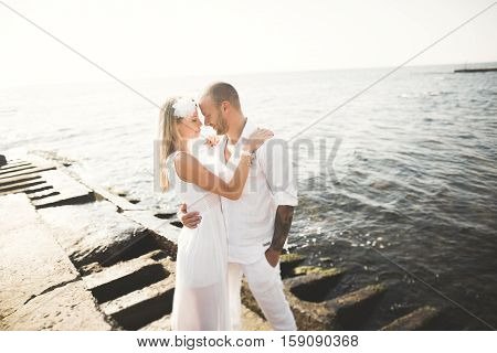 happy just married young couple celebrating and have fun at beautiful beach sunset.