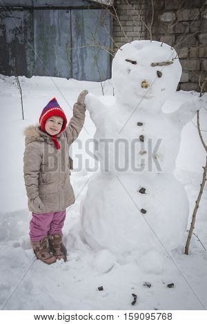 happy child girl with a snowman in winter