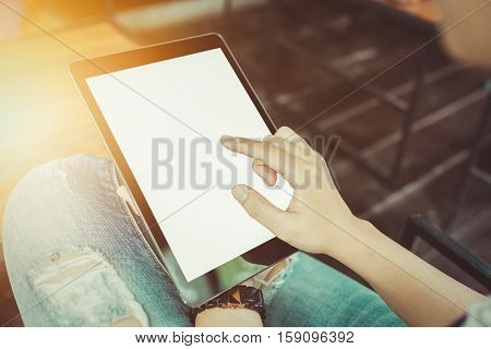 Woman hands holding and pointing on contemporary digital frame with blank screen orange sunshine vintage tone