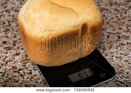 Baking bread in bread maker. Home baked bread on scales