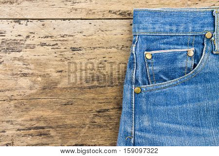 Blue jeans on brown wooden background.Close up of blue jeans Blue Jeans texture.Blue denim jeans texture. Jeans background. Blank leather jeans label sewed on a blue jeans.