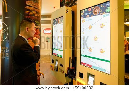HONG KONG - CIRCA NOVEMBER, 2016: a man use a Mcdonald's ordering kiosks in Hong Kong. McDonald's is an American hamburger and fast food restaurant chain.