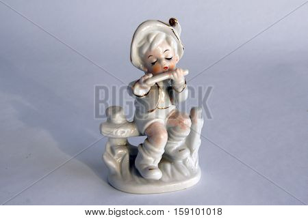 Serial porcelain figurine of a boy playing a flute from the decor store