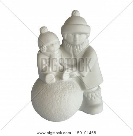 Porcelain figurine depicts children who make a snowman isolated on white. Serial porcelain from the decor store