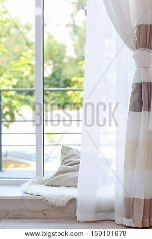 Room window with low window sill and colorful striped curtains
