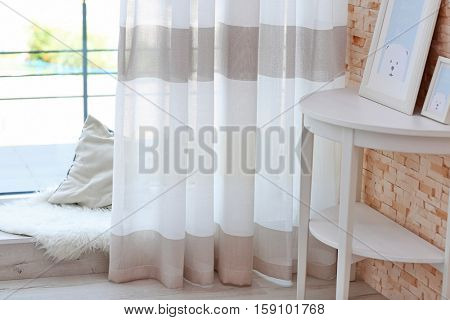 Colorful striped curtains, table and low window sill with pillow and rug