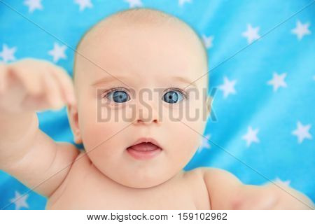 Cute baby lying on color bedspread, close up view