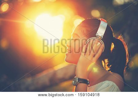 selective focus of eyebrow. Portrait of asian young woman with headphones and listening music on sunset in park.