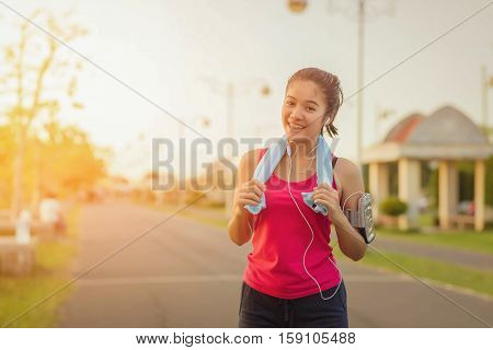 Young Woman Runner Wearing Armband And Listening To Music On Earphones.