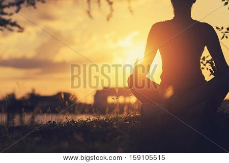 Young woman peacefully meditating in a open field. Happy young woman sitting outdoors in yoga position. Young girl practicing yoga outdoors. yoga sunset. yoga vintage. yoga in park. girl yoga relex. yoga fitness. yoga concept