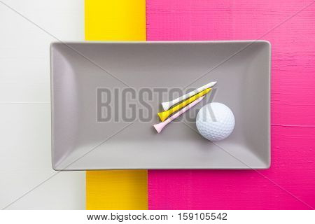 Gray ceramic dish with golf equipments on over white yellow and pink wooden table rectangle dish