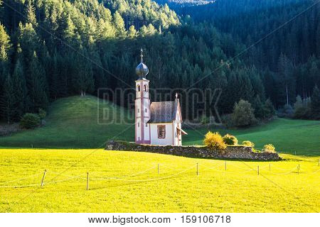 The symbol of the valley Val di Funes - church of Santa Maddalena. Tirol, Dolomites. Forested mountains surrounded by green Alpine meadows. Sunny warm autumn day