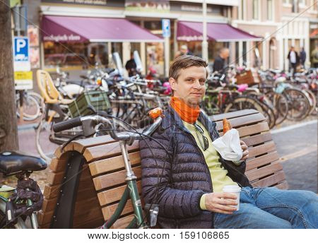 Smiling man sitting with a croissant and  take away coffee