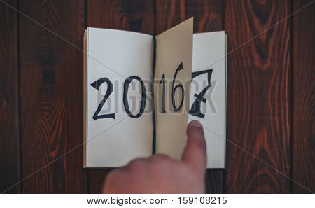 man flips notepad sheet on a wooden table. 2016 is turning, 2017 is opening. top view.