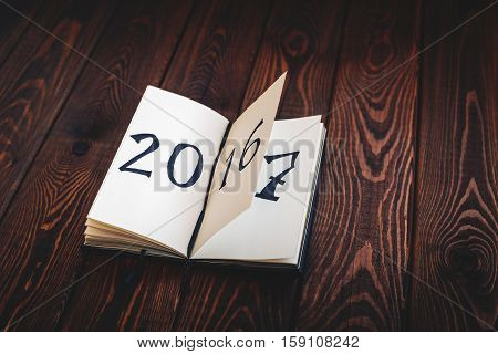 New year concept for 2017 - opened notepad on wooden rustic background, written 2016, 2017 can be seen on the next page.  Cope space