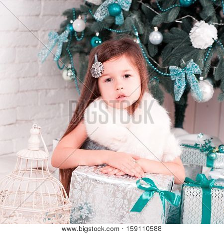 Beautiful kid girl 4-5 year old sitting with christmas decorations and boxes on white wooden floor. Posing in room. Looking at camera. Childhood. Merry christmas. Happy new year.