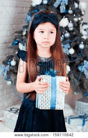 Cute baby girl 5-6 year old holding christmas gift in room. Christmas tree. Childhood. Christmas decor.