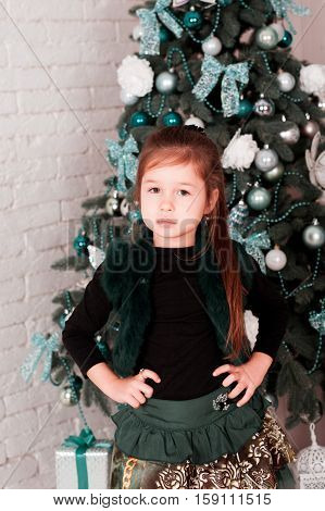 Kid girl 4-5 year old standing over Christmas tree in room. Looking at camera. Merry Christmas. Happy New Year. Celebration holidays.