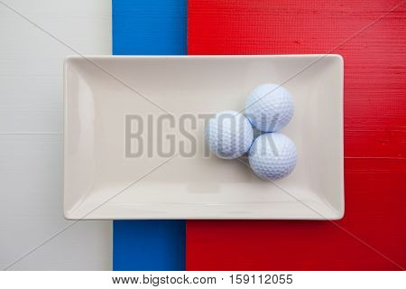 White ceramic dish with golf balls on over whiteblue and red wooden table rectangle dish
