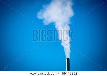 Flue and smoke on blue sky background