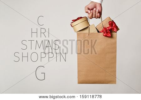 closeup of the hand of a young caucasian man holding a paper shopping bag full of gifts and the text christmas shopping forming a christmas tree