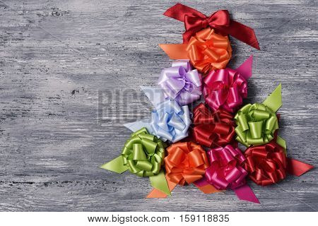 some satin gift ribbon bows of different colors forming a christmas tree on a rustic wooden background, with a negative space