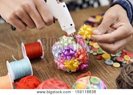 closeup of a young man making a handmade christmas ball with ribbon bows of different colors, using a hot glue gun, and a pile of different haberdashery items on a rustic wooden surface