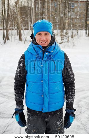 Young smiling man dressed in sports wear stands by trees and house on winter day.