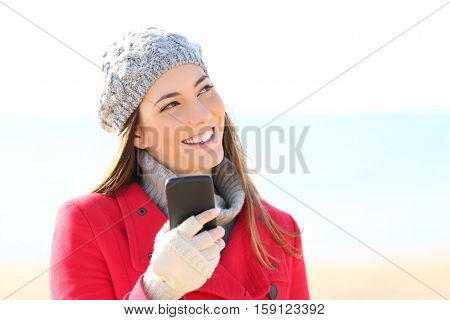 Front view portrait of a happy girl wearing coat thinking and looking sideways with a phone on the beach in winter