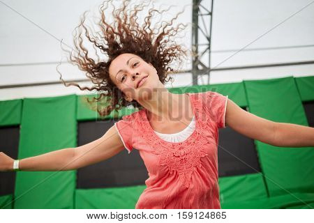 Young smiling woman jumps on trampoline attraction, half-length portrait.