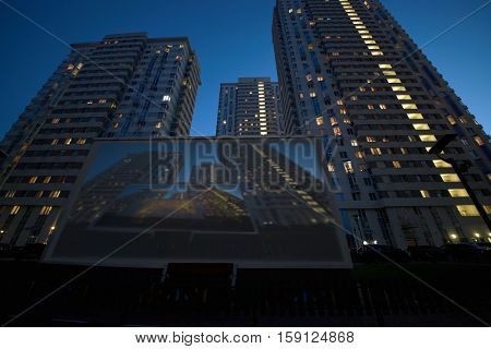 Translaion picture onto the big screen from notebook in the yard of a residential complex.