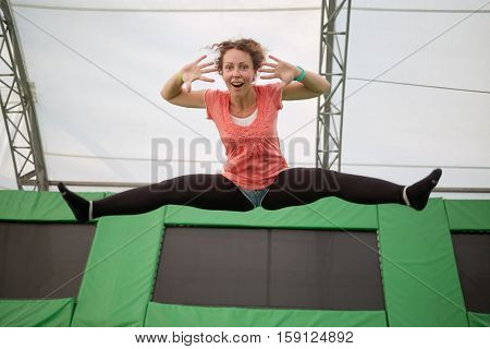 Young woman jumps on trampoline attraction making leg-split and grimacing by face.