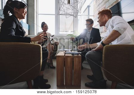 Business people in lobby sitting around the table and discussing business strategy. Businessmen and businesswomen meeting in modern office.