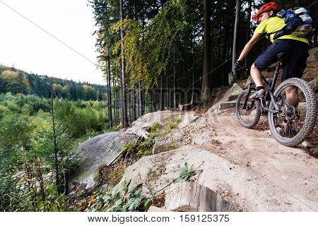 Mountain biker riding on bike in autumn inspirational mountains landscape. Looking at beautiful fall woods. Man cycling MTB on enduro trail track. Sport fitness motivation and inspiration.